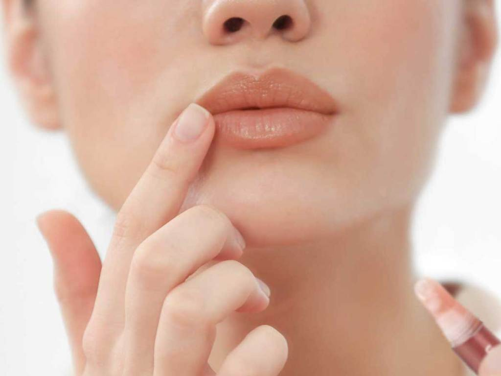 woman putting lip gloss on her lips