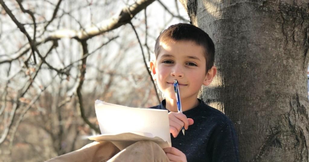 boy doing homework in tree