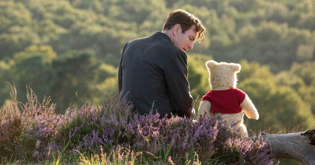 Christopher Robin and Winnie the pooh sitting in the grass