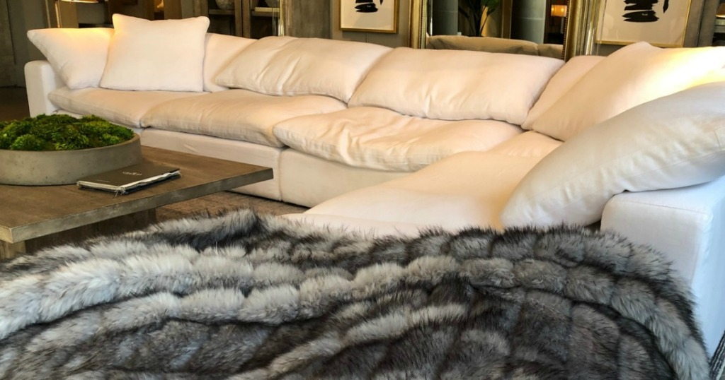 white cloud couch with blanket and coffee table