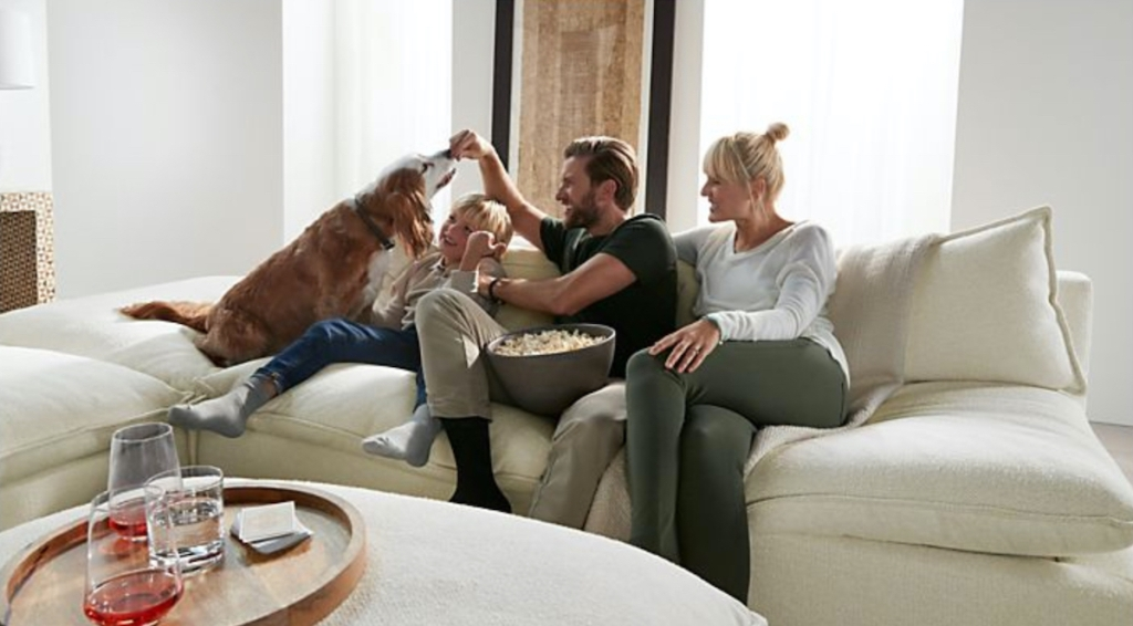 family and dog sitting on cream colored sectional couch laughing