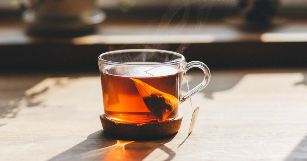 clear glass cup of hot tea with steam rising