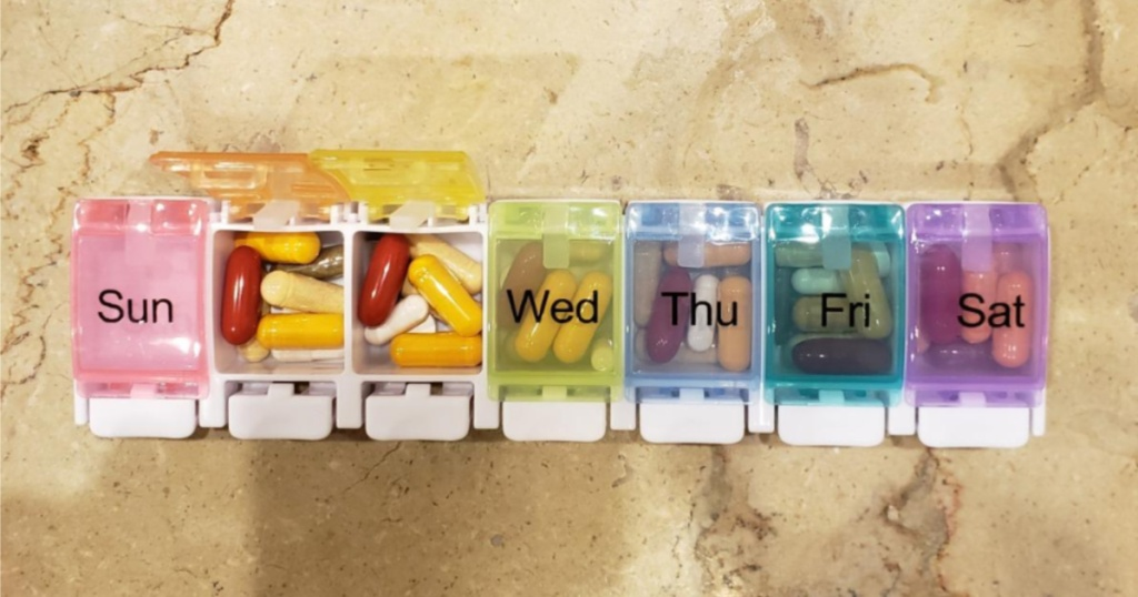 multi-color weekly pill organizer on marble surface