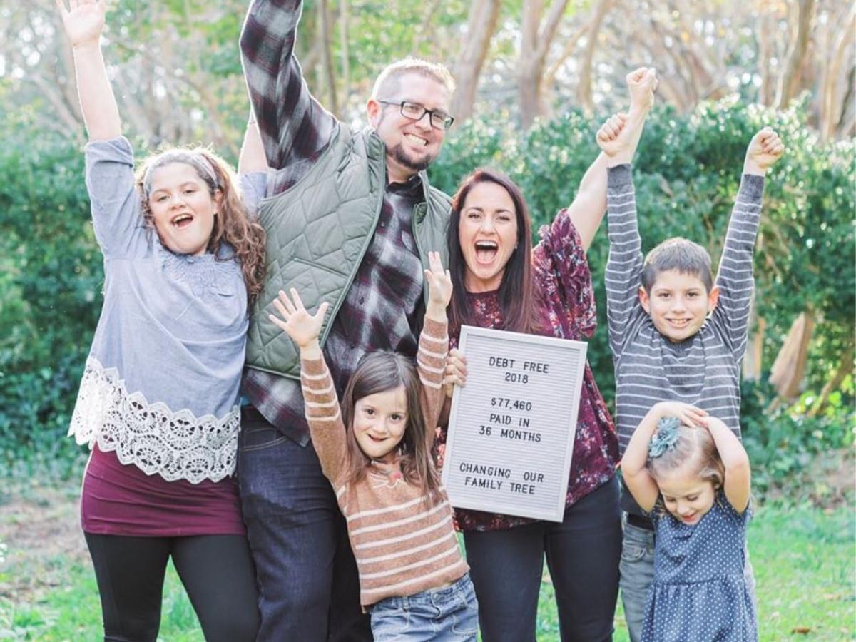 family celebrating their debt free status outside