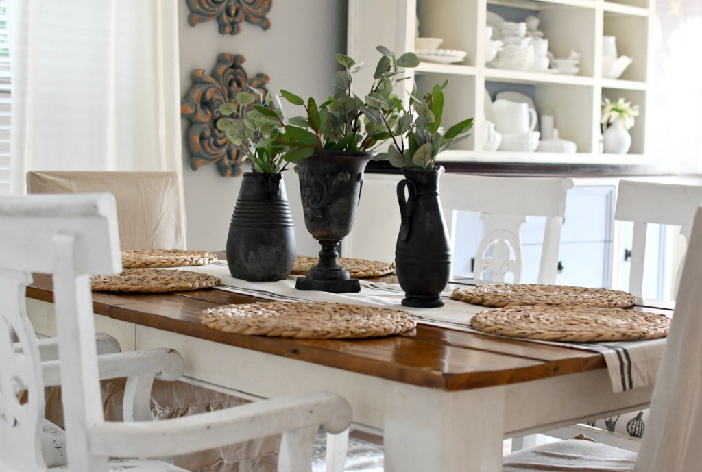 dining table with black vases and greenery