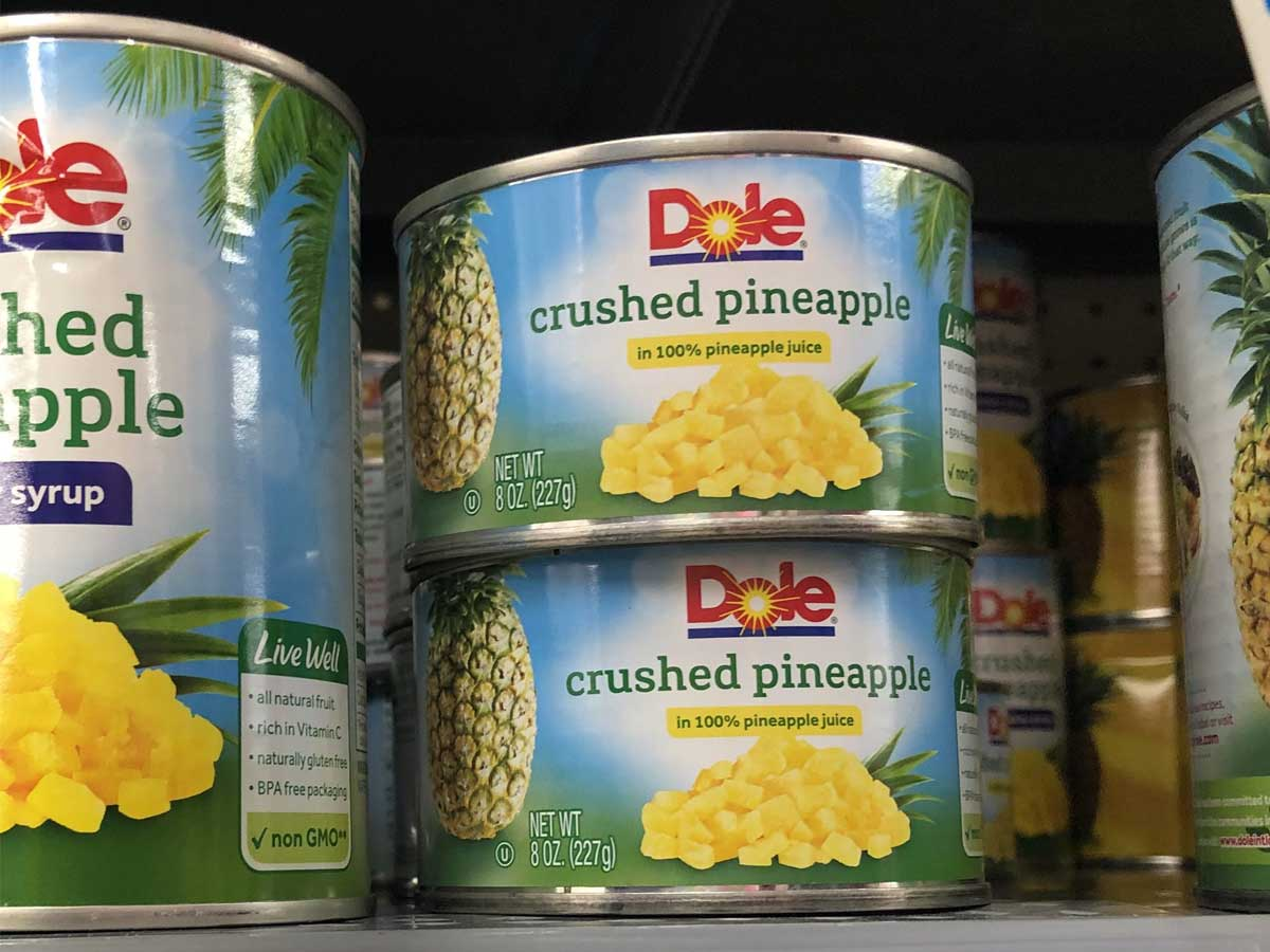 dole crushed pineapple cans on shelf in store