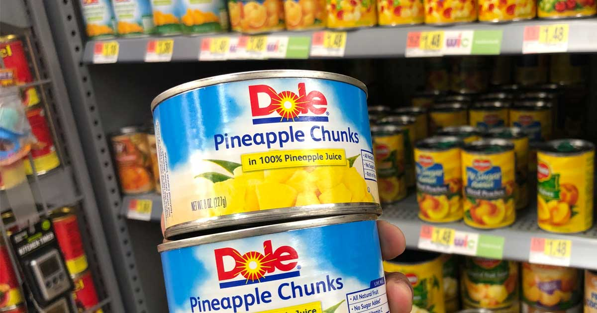 hand holding cans of pineapple chunks in store