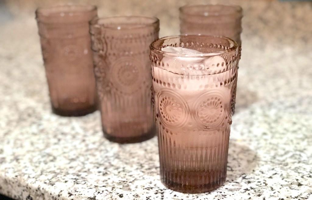 four purple pink drinking glasses sitting on granite countertop
