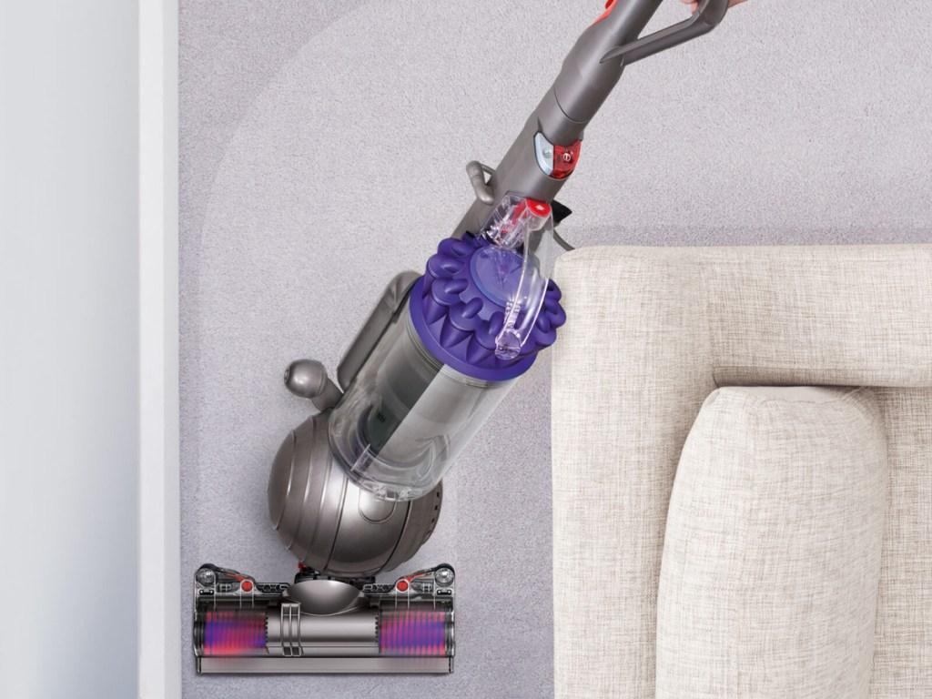purple and gray vacuum vacuuming carpet around white couch