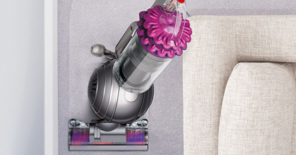 fuchsia dyson vacuuming carpet by white couch