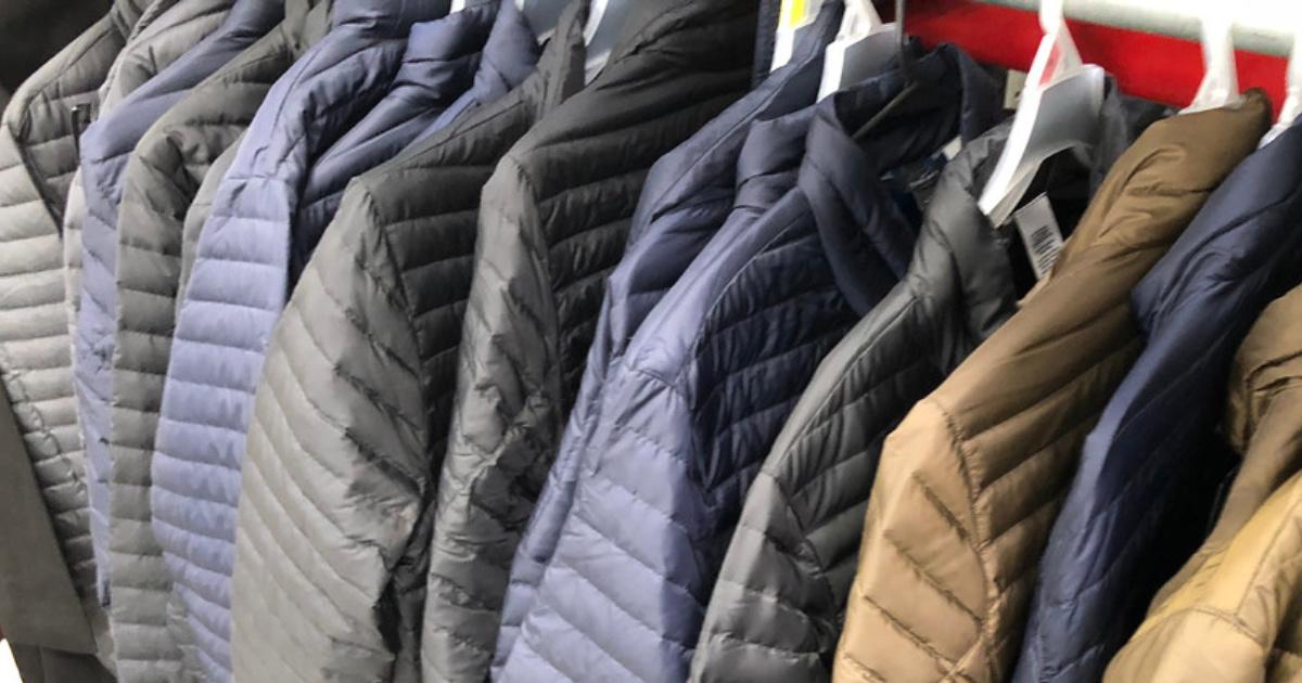 row of men's winter coats on hangers in a store