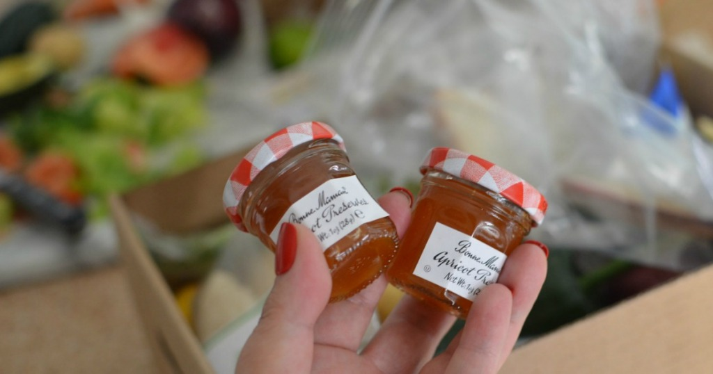 holding mini apricot jams with everplate meal box in the background