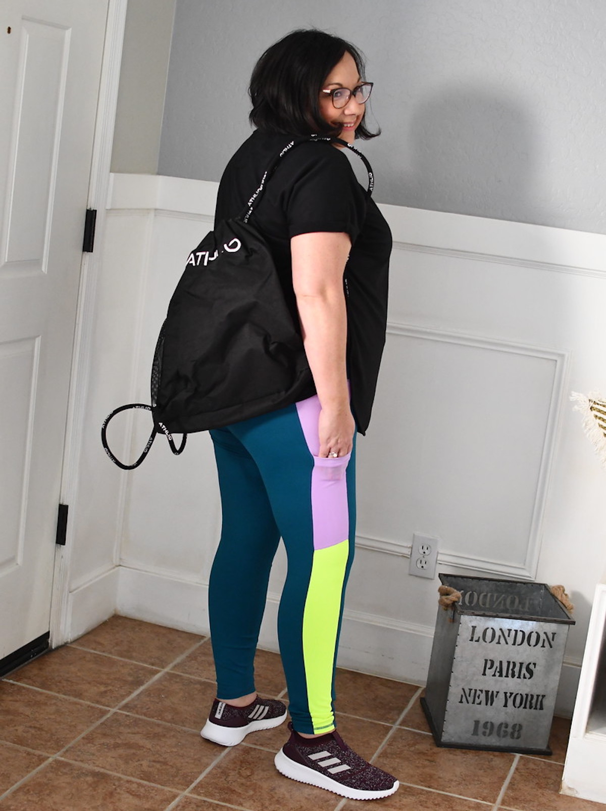 lina wearing neon colored leggings with black backpack on shoulder