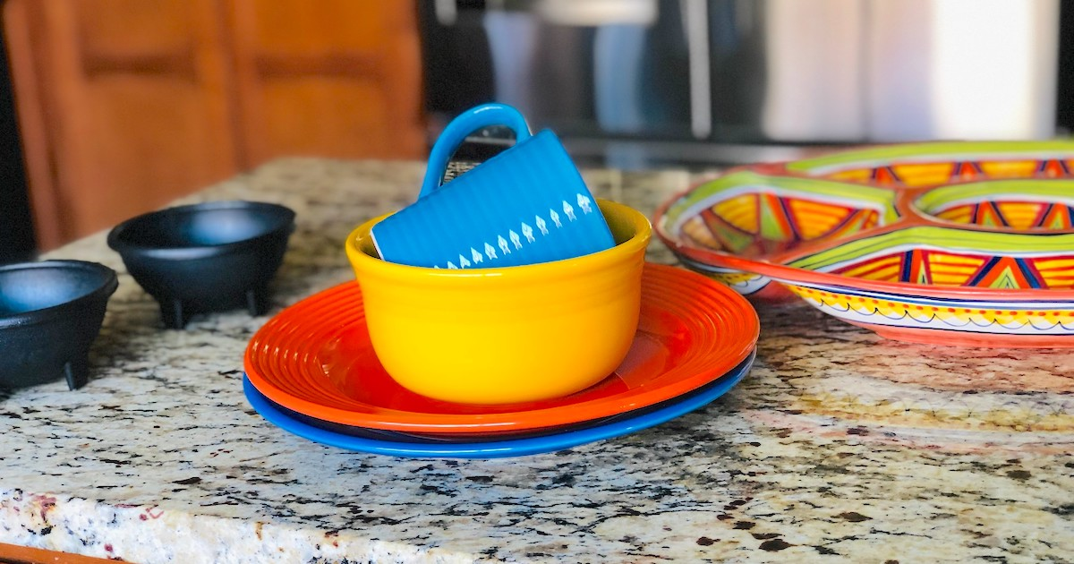 blue orange and yellow dishes on granite countertop
