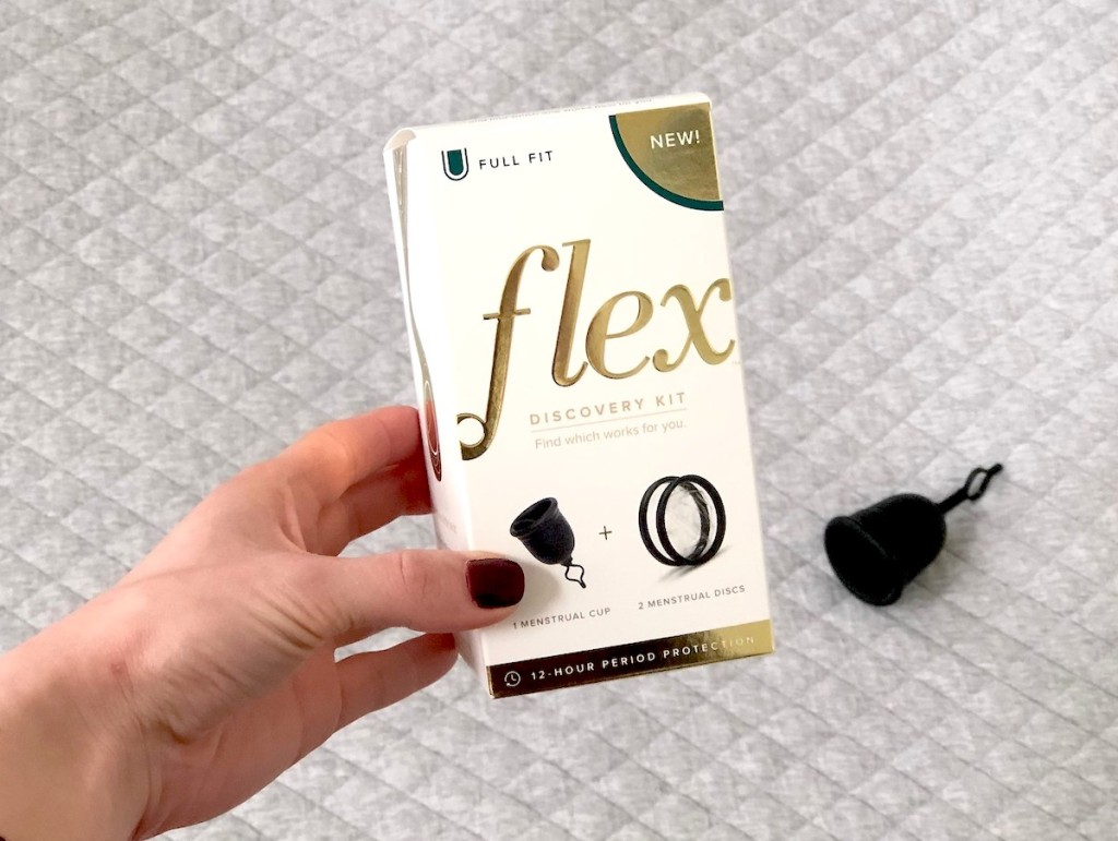 hand holding a box with flex menstrual cup on blanket