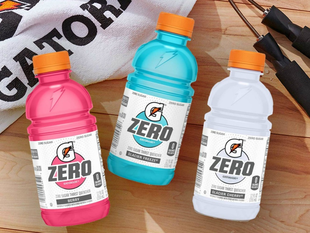 three bottles of sports drinks on table by towel