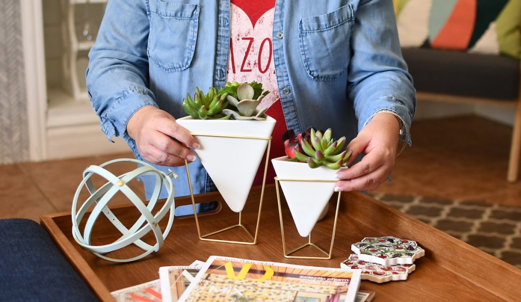 woman holding two white geometric vases with succulents