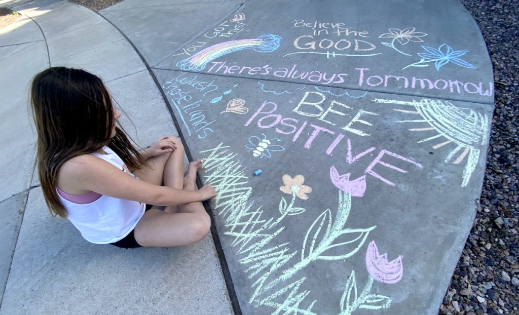girl writing messages using sidewalk chalk