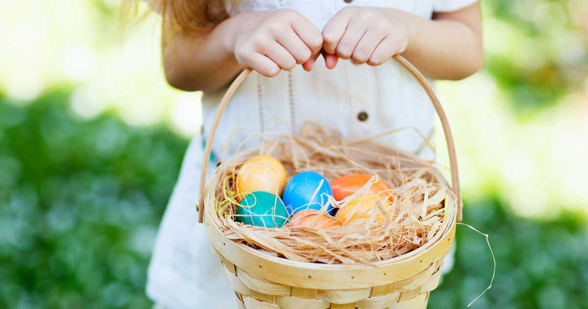 young girl holding a basket with easter eggs