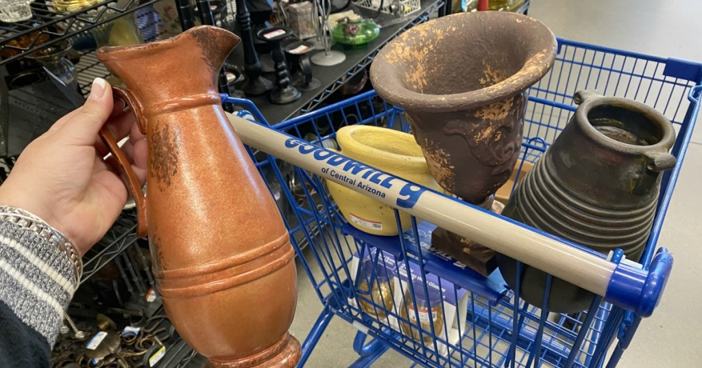 goodwill pottery pieces in a shopping cart