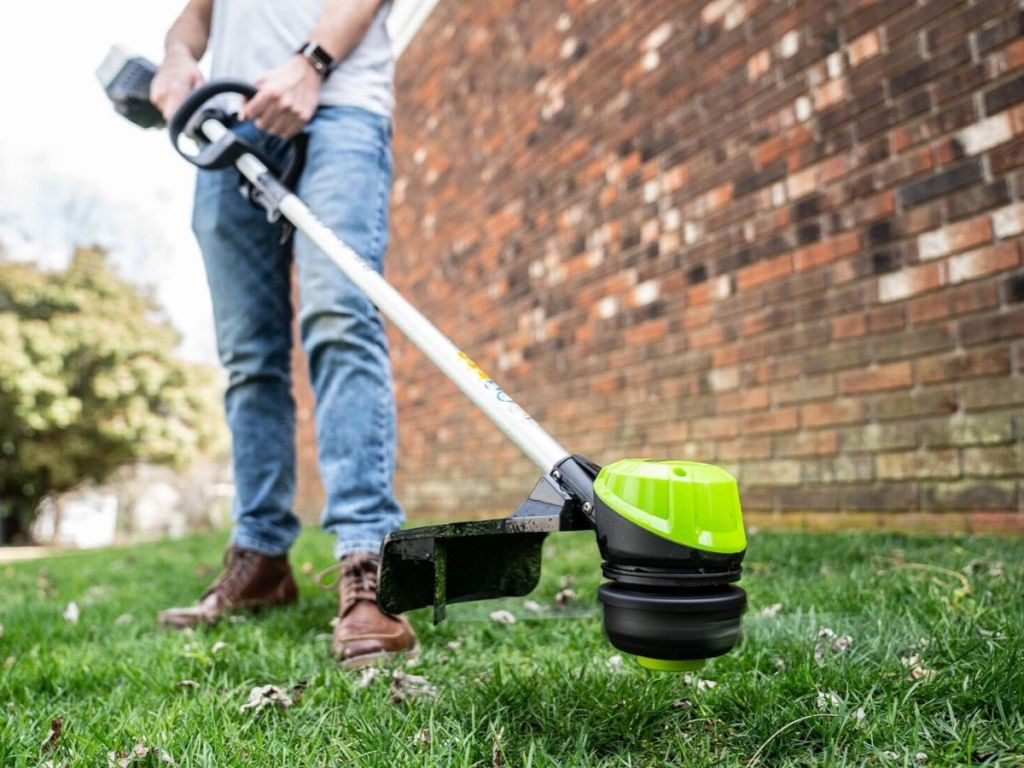 mans lower body using cordless trimmer outside brick home