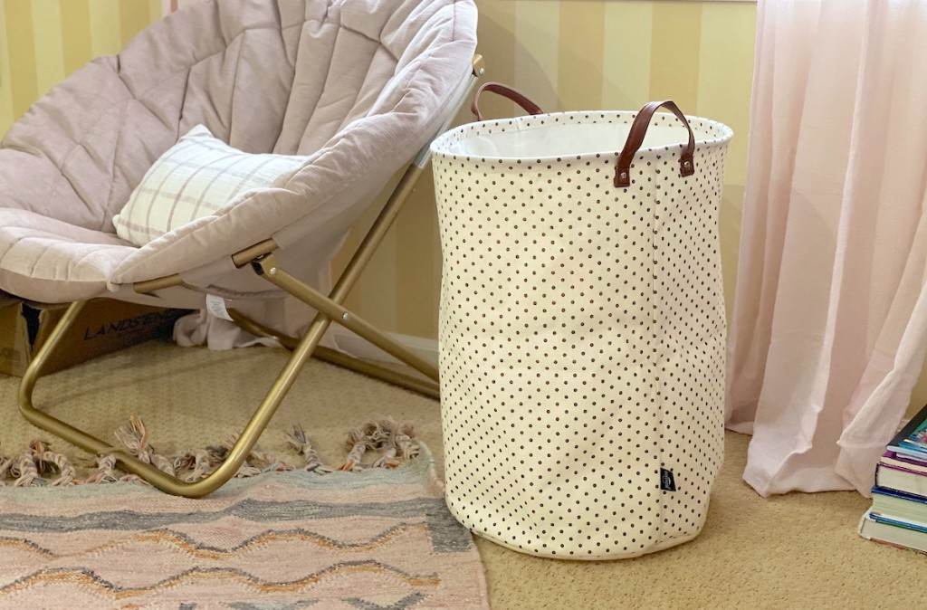 white polka dot clothes hamper sitting in room next to teen chair