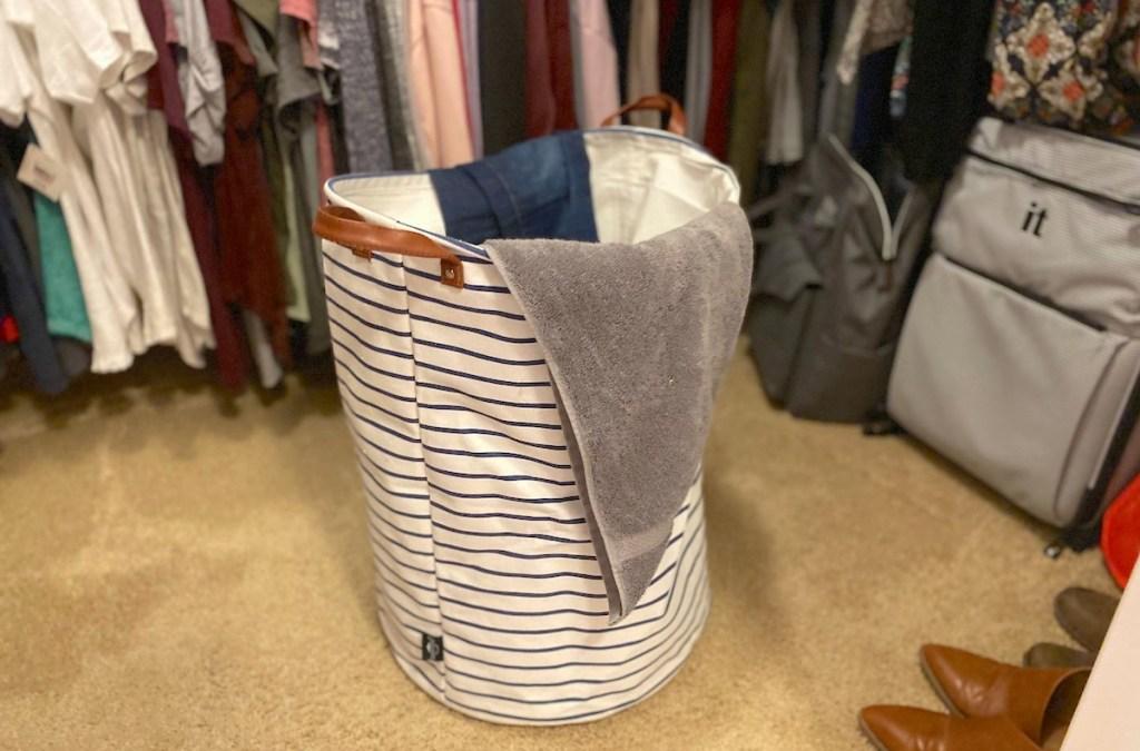 stripe clothes hamper sitting in closet