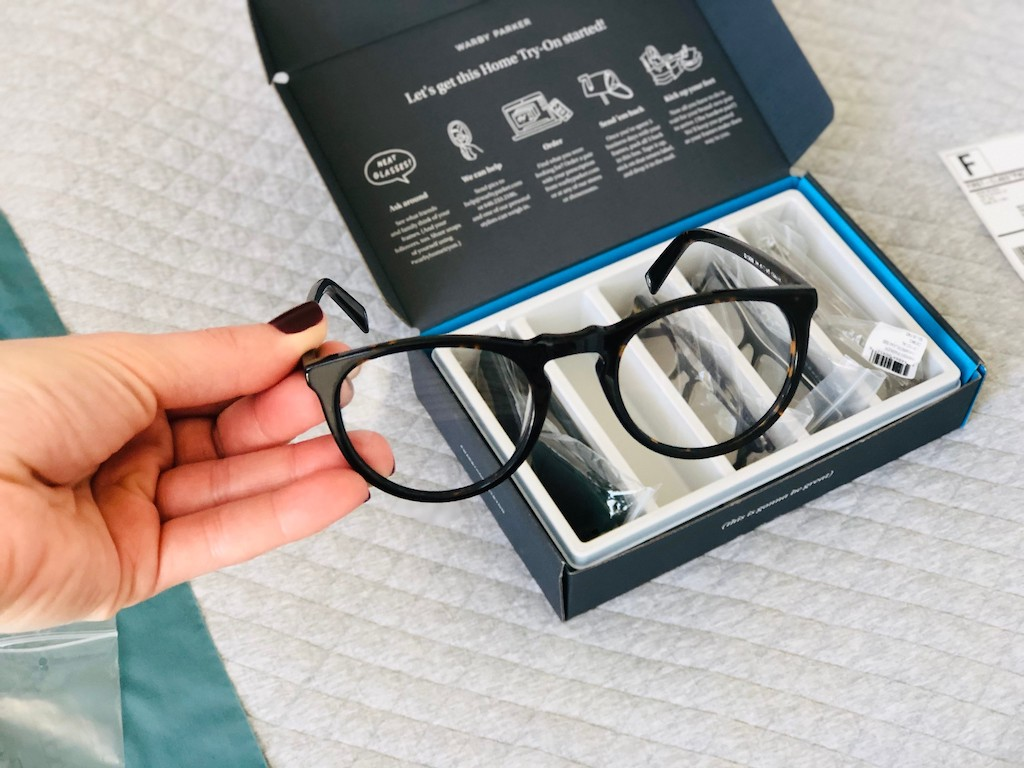 holding eyeglasses in front of a Warby Parker box