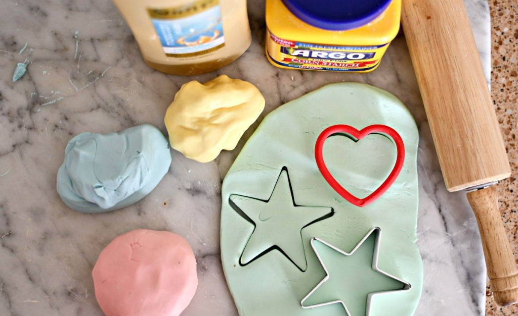 homemade play-dough on a cutting board with cookie cutters