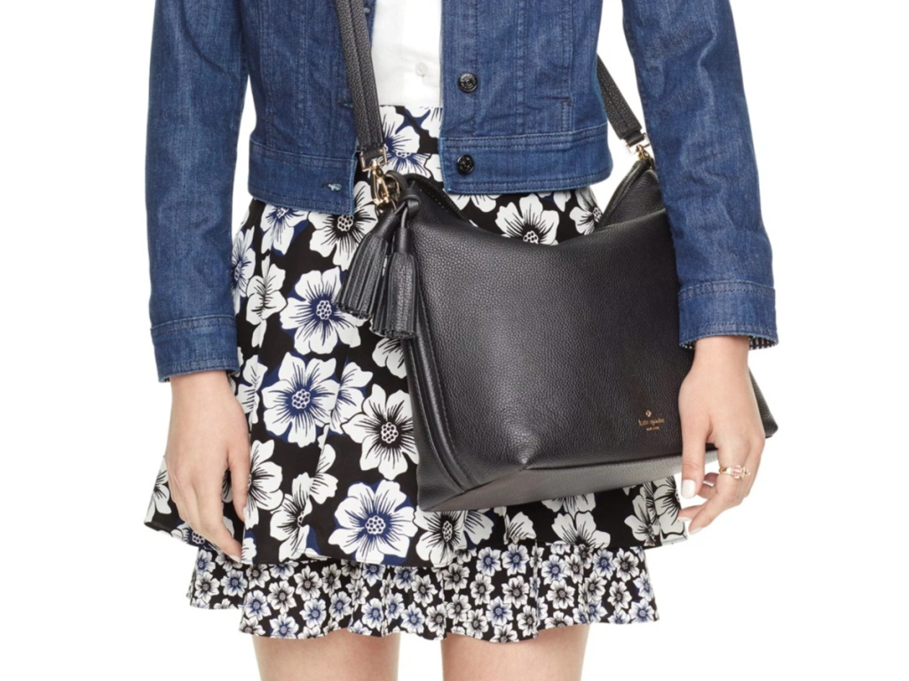 woman in denim jacket and black/white floral skirt carrying black kate spade bag