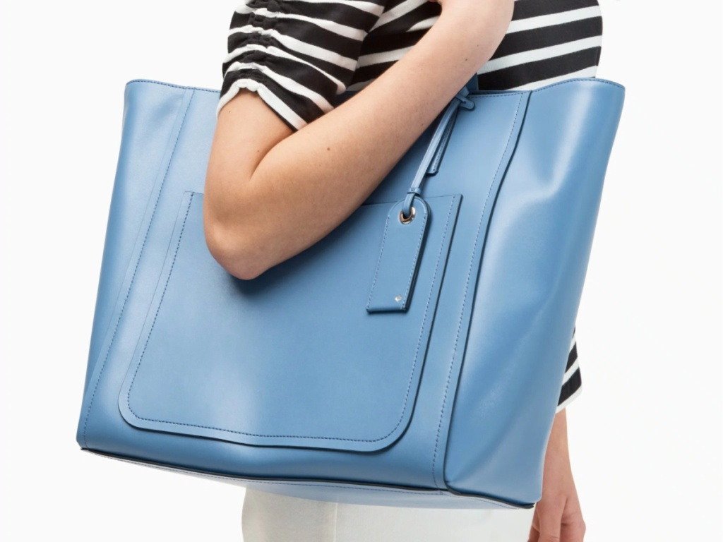 woman wearing blue and white stripe shirt carrying blue tote bag