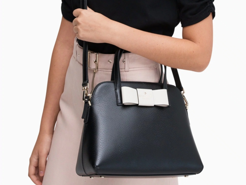 woman wearing black shirt and pink skirt carrying black bag with white bow