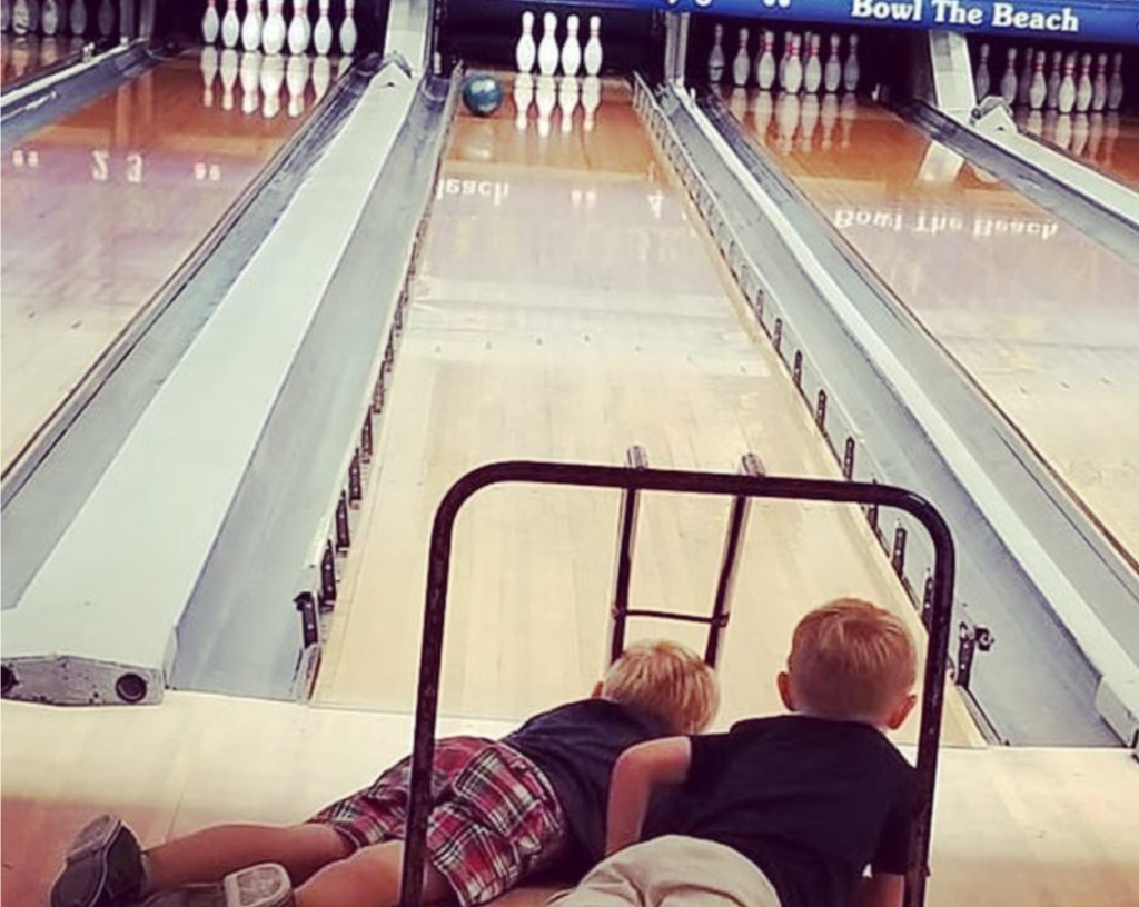 two boys laying down watching bowling ball go down the lane