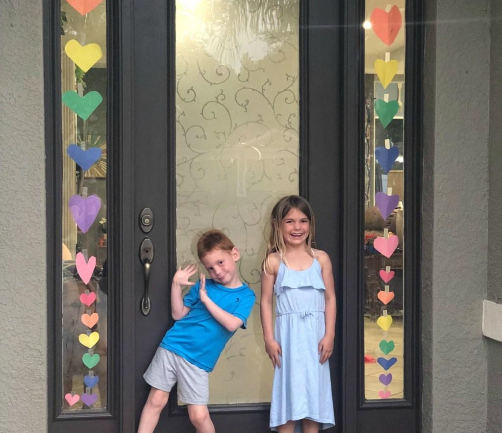 kids decorating door with hearts during coronavirus