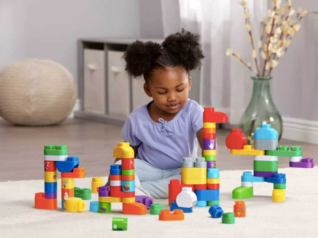 little girl playing with blocks on the floor