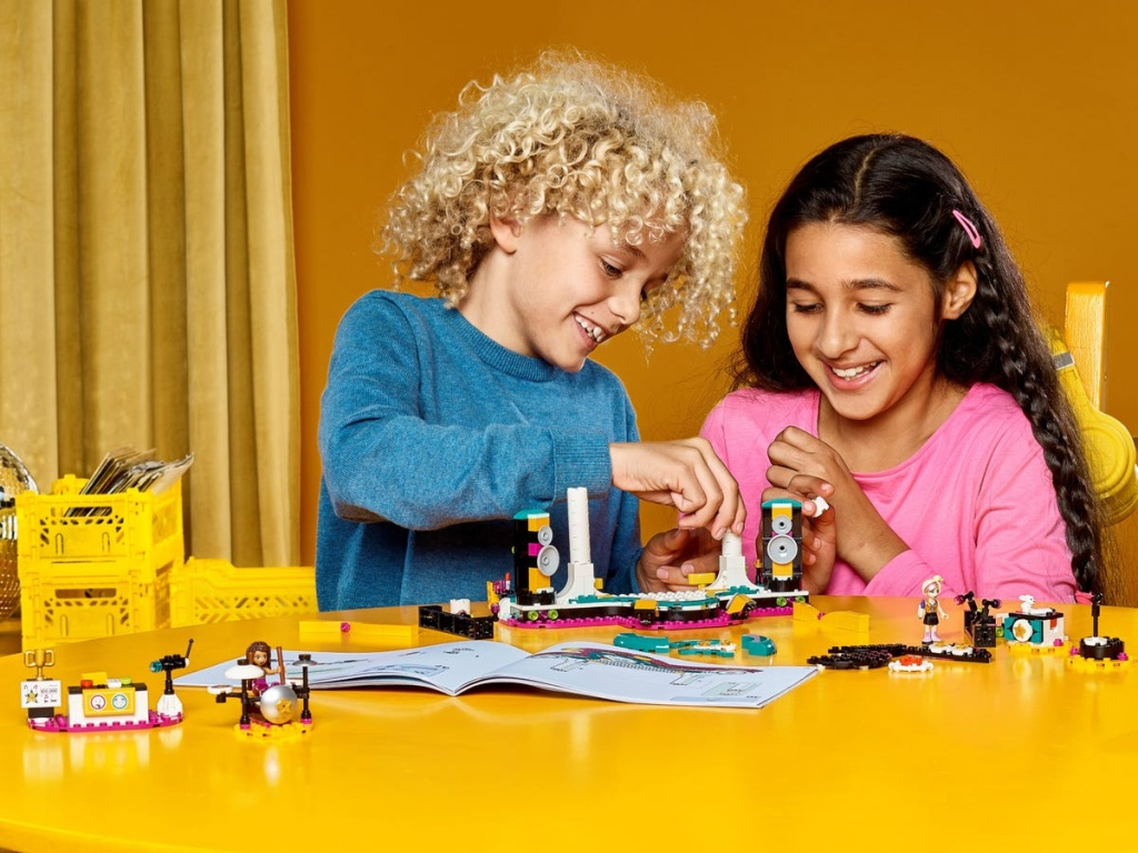 two kids playing with a lego set