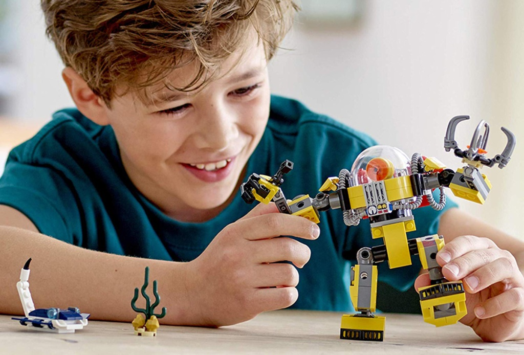 boy playing with lego robot