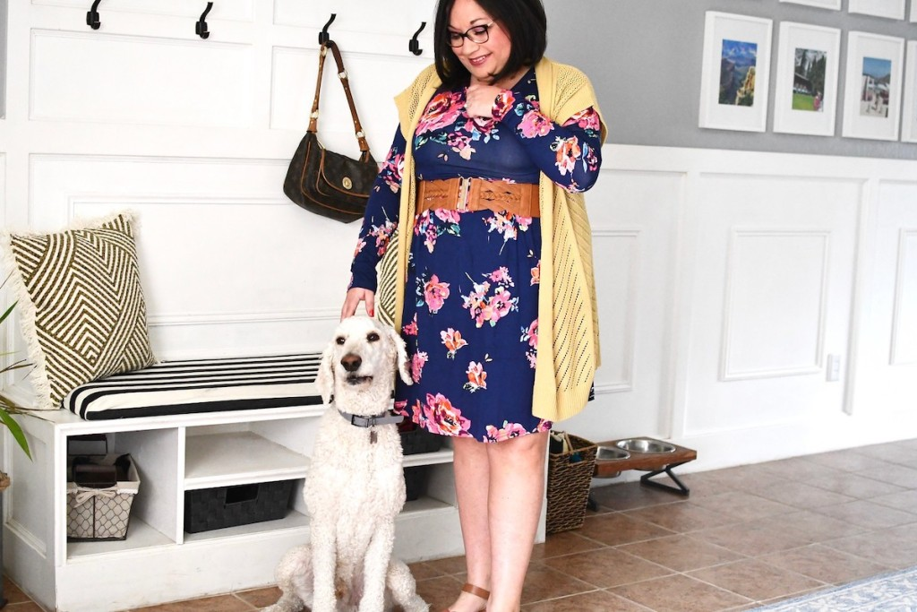 woman wearing floral dress in foyer petting dog