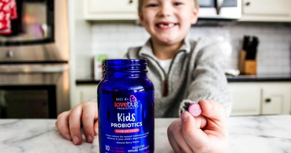 little boy holding pill by bottle in kitchen