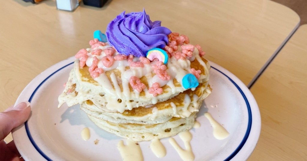 pancakes topped with cereal and purple icing