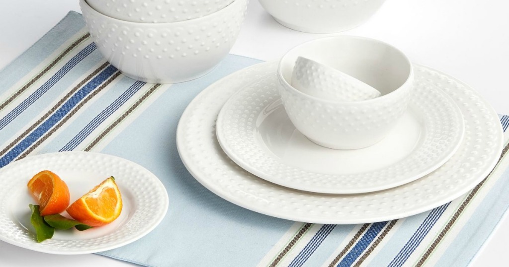 white dishes on colorful placemat and orange wedge