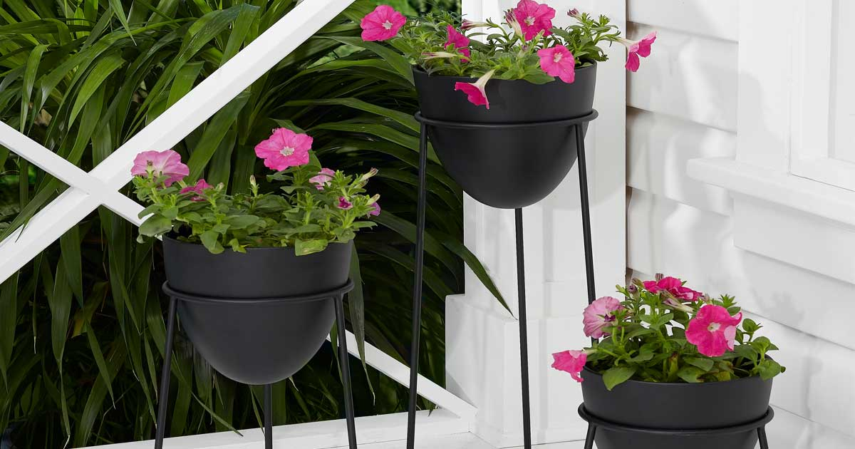 set of three black planters on a porch with flowers in them