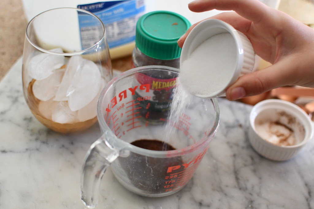 making whipped iced coffee and adding sugar to measuring cup