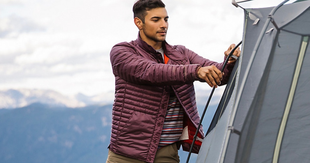 man wearing maroon puffy jacket putting up tent