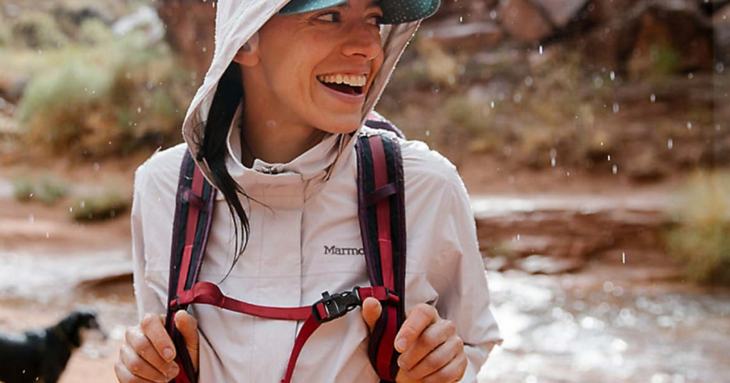 girl wearing Marmot jacket and holding onto backpack straps with water in background
