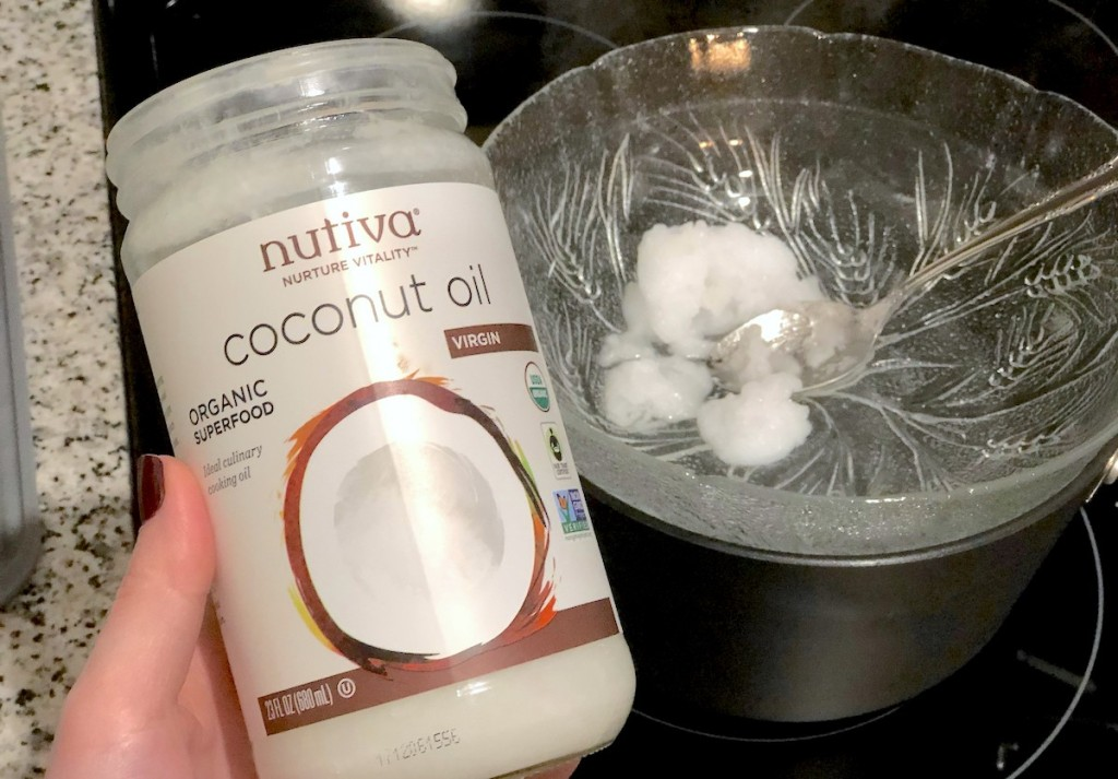 hand holding an open jar of coconut oil next to bowl of melting oil