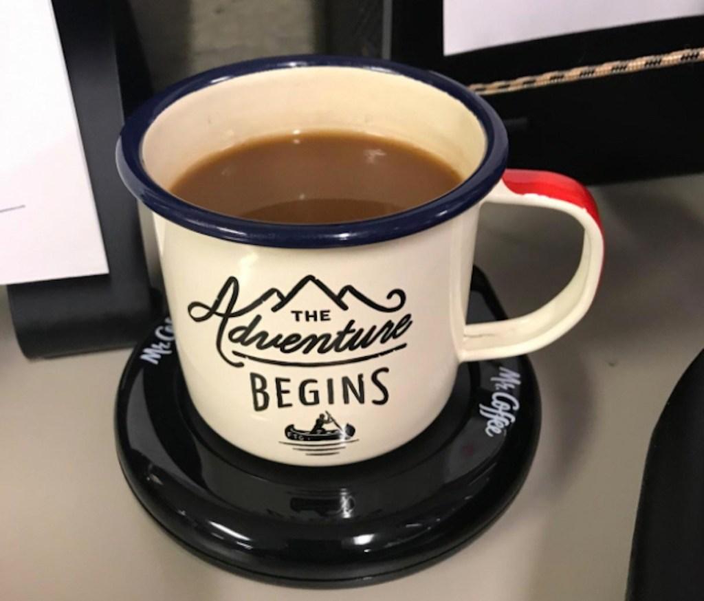 adventure mug sitting on black mug warmer on desk