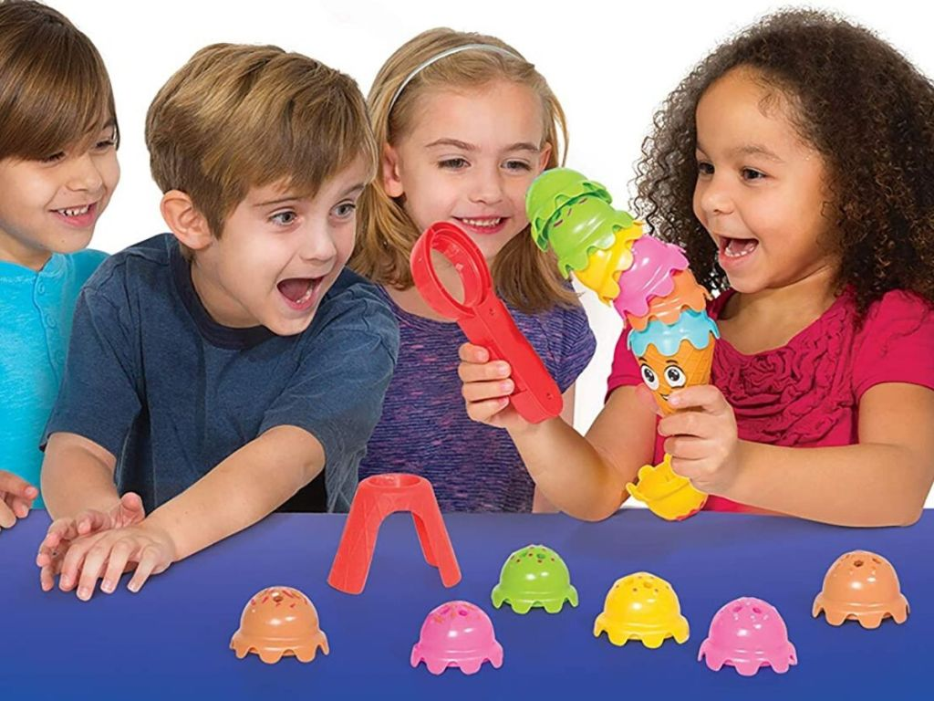 four kids playing game with plastic ice cream scoops to stack with splastic ice cream scooper