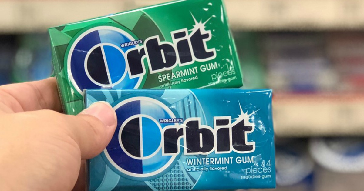 hand holding two packs of Orbit gum in a store