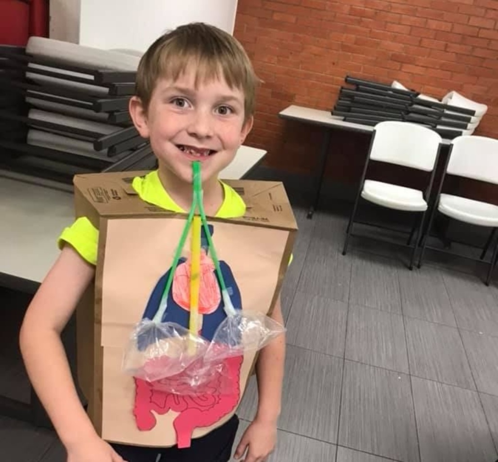 boy wearing paper bag with cutouts of organs glued on it
